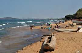 FILE -  People wash clothes on Saga Beach as traditional boats are left by the seaside, at Lake Malawi, July 17, 2011.