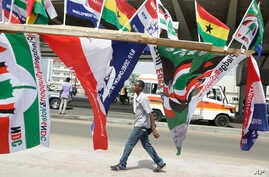 A man walk past election campaign flags on a street in Accra, Ghana, Dec. 6, 2016. Polls will open Dec. 7 at 0700 UTC.