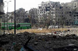 This May 7, 2014 photo provided by the anti-government activist group Coordination Committee of Khalidiya Neighborhood in Homs, which has been authenticated based on its contents and other AP reporting, shows green buses carrying Free Syrian Army fig
