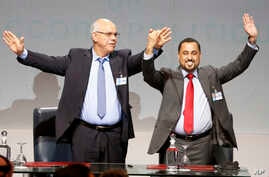 Mohammed Chouaib, head of delegation from the U.N.-recognized government in the eastern city of Tobruk, Libya, left, and Dr. Saleh Almkhozom, Second Deputy Chairman of the Libyan General National Congress, react after signing a U.N.-sponsored deal ai
