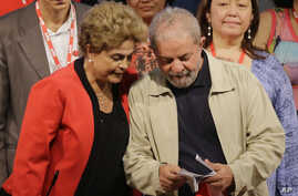 Brazil's former President Luiz Inacio Lula da Silva, right, looks at a document with Brazil's President Dilma Rousseff during a Central Workers Union convention in Sao Paulo, Brazil, Tuesday, Oct. 13, 2015.