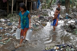 Children carry plastic containers of potable water as they wade through debris and mud brought by Typhoon Rammasun in Batangas city, south of Manila, July 17, 2014.