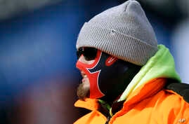 A fan is bundled against the cold weather at an NFL football game between the New England Patriots and the New York Jets, Dec. 31, 2017, in Foxborough, Mass.
