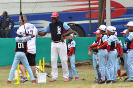Tampa Bay Rays hitting coach Derek Shelton, left, and retired Cuban player Michel Ford (25) hold a baseball clinic for Cuban children the day before the Rays are to play an exhibition game against the Cuban National Team in Havana, Cuba, March 21, 20