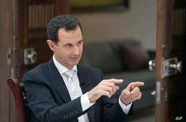 FILE - In this file photo released by the Syrian official news agency SANA, Syrian President Bashar Assad speaks during an interview with the Greek Kathimerini newspaper, in Damascus, May 10, 2018.