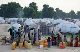 FILE- People displaced by Islamist extremists fetch water at the Muna camp in Maiduguri, Nigeria.