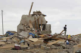 Shiite fighters known as Houthis stand on the rubble of a house destroyed by a Saudi airstrike in Sanaa, Yemen, Wednesday, Aug. 26, 2015.