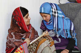 Pakistani teenage activist Malala Yousafzai (L), who was shot in the head by the Taliban for campaigning for girls' education, talks to Syrian refugee Mazoon Rakan, 16, about Mazoon's experience in the camp during her visit to the Zaatri refugee camp