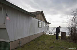 FILE - Tim Betts removes a horseshoe pit that he recently built at his family's beachfront home that is sitting off of its foundation in Washaway Beach, Washington.