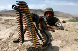 An Afghan National Army soldier holds a position while patrolling the village of But Khak on the outskirts of Kabul, May 15, 2012.