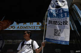 A volunteer displays a banner on a street to raise awareness of an unofficial referendum in Macau, Aug. 24, 2014.