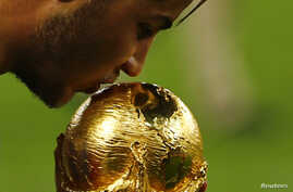 Germany's Mario Goetze kisses the World Cup trophy as he celebrates their 2014 World Cup final win against Argentina at the Maracana stadium in Rio de Janeiro, July 13, 2014.
