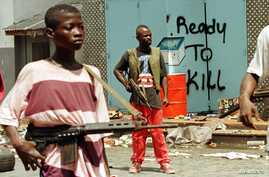 FILE - Street fighters with ULIMO-J walk  past graffiti in the Liberian capital of Monrovia in this May 1996 photo.