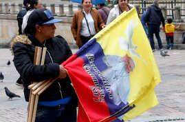 A woman sells flags with the image of Pope Francis outside the Cathedral of Bogota in Bolivar Square, Colombia, Sept. 2, 2017.