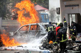 Somali firemen try to extinguish burning cars at the scene where a car bomb exploded in front of a restaurant in Mogadishu, Somalia January 29, 2019.