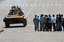 Kyrgyz soldiers on an armored vehicle drive past a group of people in Osh on 11 Jun 2010
