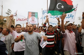 Protesters wave a Libyan flag as they demonstrate in Martyrs' Square demanding deposed Libyan dictator Moammar Gadhafi -era officials be banned from taking up political posts, in Tripoli, May 5, 2013.