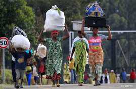 People displaced by fighting between Congolese forces and M23 rebels make their way home after spending a night in the Ugandan town of Bunagana, Oct. 31, 2013.