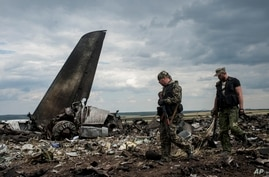 Pro-Russian fighters walk past remnants of a downed Ukrainian army aircraft Il-76 at the airport near Luhansk, Ukraine, June 14, 2014.