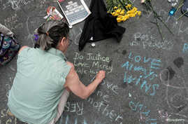 A woman writes a message on the street commemorating the victims at the scene of a car attack on a group of counter-protesters during the a white supremascist rally in Charlottesville, Virginia, Aug. 14, 2017.