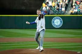 Singer and hip-hop artist Macklemore throws out the first pitch of a baseball game between the Seattle Mariners and the Kansas City Royals, Friday, April 29, 2016, in Seattle.