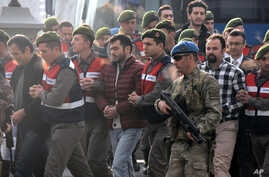Paramilitary police escort the defendants as a trial opened in Mugla, southern Turkey, Monday, Feb. 20, 2017, for 47 people accused of attempting to kill President Recep Tayyip Erdogan on the night of the failed coup, while he was vacationing with hi