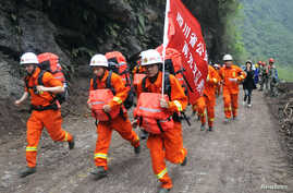 Rescuers run through wreckage to reach the isolated Baoxing county a day after an earthquake hit Ya'an, Sichuan province Apr. 21, 2013.