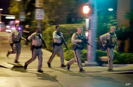 FILE - Police run toward the scene of a shooting near the Mandalay Bay resort and casino on the Las Vegas Strip in Las Vegas, Oct. 1, 2017.