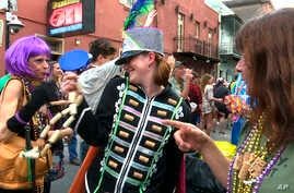 FILE - Image made from video shows a woman wearing a marching band costume taunts revelers with trinkets and beads in the Krewe of Cork parade in New Orleans, Feb. 22, 2019.