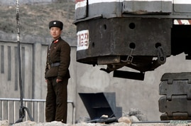 A North Korean soldier stands guard on the banks of Yalu River, near the North Korean town of Sinuiju, opposite the Chinese border city of Dandong, April 10, 2013.