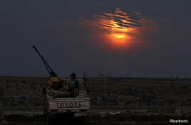 A Free Syrian army fighter sits on a pick-up truck mounted with a weapon, as the supermoon partly covered by clouds is seen in the background, in the west of the rebel-held town of Dael, in Deraa Governorate, Syria, Nov. 14, 2016.