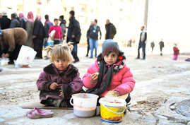 Girls eat a cooked meal provided by the U.N. through a partner NGO in the east Aleppo neighborhood of al-Bab, Syria, in this handout picture provided by UNHCR, Jan. 4, 2017.