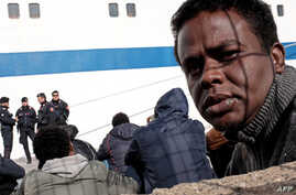 Migrants wait at the port of Lampedusa to board a ferry bound for Porto Empedocle in Sicily, Italy, Feb. 20, 2015.