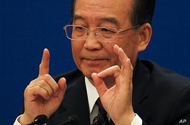 Chinese Premier Wen Jiabao gestures as he answers questions during a press conference after the closing session of the annual National People's Congress in Beijing's Great Hall of the People, China, Monday, March 14, 2011. (AP Photo/Ng Han Guan)