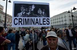 "A man holds a placard displaying pictures of Spanish late dictator Francisco Franco and Germany's late dictator Adolf Hitler during a demonstration titled ""NiValleNiAlmudena, Madrid sin Franco"" (Madrid without Franco) in Madrid, Oct. 25, 2018, agains"
