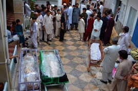 FILE - Pakistani Shi'ite Muslims gather around bodies of the victims of a suicide bombing for which the Sunni militant group Lashkar-e-Jhangvi claimed responsibility, in Quetta, Pakistan, July 1, 2013.