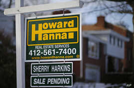 A for sale sign hangs in front of a house in Mount Lebanon, Pennsylvania, Jan. 9, 2014.