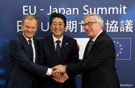 FILE - Japan's Prime Minister Shinzo Abe, center, is welcomed by European Council President Donald Tusk, left, and European Commission President Jean-Claude Juncker at the start of a European Union-Japan summit in Brussels, July 6, 2017.