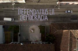 "Seen from above, a sign covering a street forms the Spanish phrase: ""We defend democracy,"" made with photographs of the president and his cabinet, outside the Constitutional Court in Guatemala City, Jan. 9, 2019. Guatemala's highest court has blocked"
