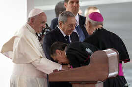 A member of Cuba's church leadership kisses the hand of Pope Francis as Cuban President Raul Castro stands alongside him during the pope's arrival ceremony at the airport in Havana, Sept. 19, 2015.
