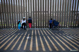 People hold conversations through the U.S. Mexico border wall at Border Field State Park in San Diego, California, Nov. 18, 2017.
