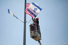 A worker hangs Israeli and American flags on a lamppost along a freeway leading to Jerusalem, days before a planned visit by President Donald Trump, May 16, 2017.