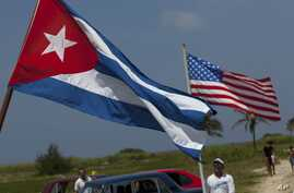 FILE - People from the local nautical club carry a Cuban and a U.S. flag to the coast to watch U.S. swimmer Diana Nyad start her swim to Florida from Havana, Cuba.