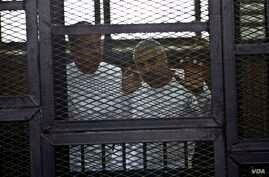 Al-Jazeera English bureau chief Mohammed Fahmy, right, and correspondent Peter Greste, appear in a defendant's cage in a courtroom in the Police Institute Court House in Tora, along with several other defendants during their trial on terror charges,