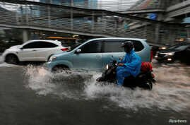People ride their motorcycles through a flooded street in a business district in Jakarta, Indonesia, Dec. 11, 2017.
