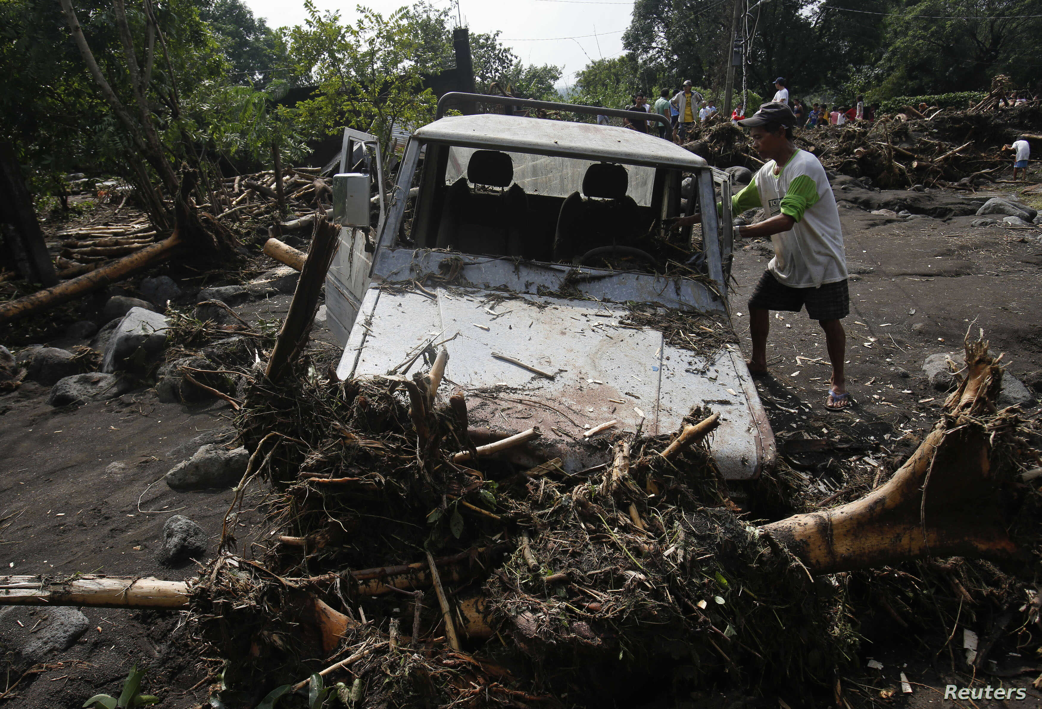 A man removes debris from his vehicle along a road in Arayat, Pampanga, that was hit by Typhoon Nari in the northern Philippines, October 13, 2013.