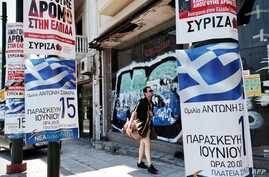 A man passes by election posters of the conservative new Democracy party and the left coalition Syriza party in central Athens, June 13, 2012.