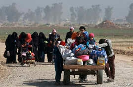 FILE - Iraqi civilians walk toward Iraqi security forces after fleeing their homes due to fighting between government forces and Islamic State militants, on the western side of Mosul, Iraq, March 9, 2017.