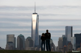 FILE - A couple look out at New York's Lower Manhattan and One World Trade Center from Liberty State Park in Jersey City, New Jersey.