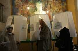 Georgians leave voting booths to cast their ballots during the presidential election in Tbilisi, Georgia, Oct. 27, 2013.
